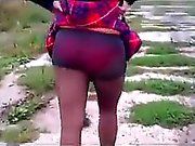 Bootylicious brunette in a tiny plaid skirt walks the stree