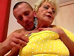 Busty granny enjoying hard sex with young man