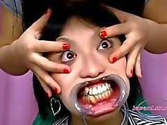 Cute Asian Girl gets her face stretched with toys