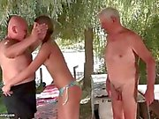 Teen enjoys sex with two older men in the outdoor wilderness