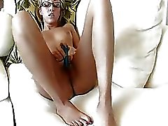 A sexy blonde wearing glasses masturbating with a vibrator
