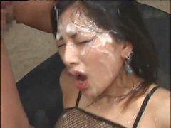Asian seductress in fishnet lingerie enjoys a cum shower at a bukkake session