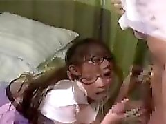 Cute schoolgirl sits on the bed while she gives him a blowj
