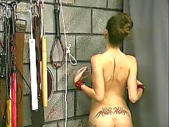 A tattooed slut is naked bound and displined